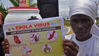A Liberian woman holds up a pamphlet with guidance on how to prevent the Ebola virus from spreading, in the city of Monrovia, Liberia - 14 August 2014