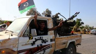 An Islamist fighter from the Fajr Libya (Libyan Dawn) coalition flashes the V sign for victory at the entrance of Tripoli international airport on 24 August 2014