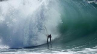 """A swimmer catches a wave at """"The Wedge"""" wave break in Newport Beach, California 27 August 2014"""