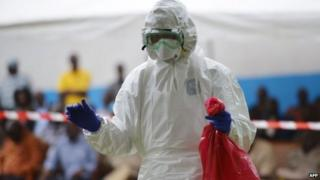 A man prepares to take off his protective suit at Biankouma's hospital during a simulation, on August 14, 2014.