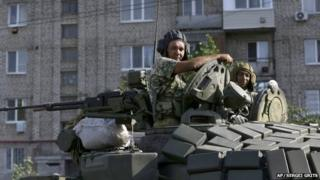 Pro-Russian rebels ride on a tank in the town of Krasnodon, eastern Ukraine, Sunday, Aug. 17, 2014. A column of several dozen heavy vehicles, including tanks and at least one rocket launcher, rolling through rebel-held territory on Sunday