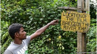 A Sri Lankan guide points to a sign at Kelani River at Kitulgala, where the film Bridge on the River Kwai was filmed. August 2014