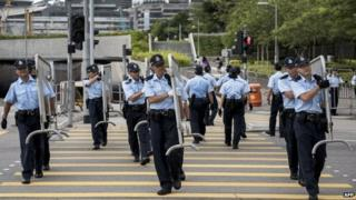 Police officers carry barriers outside Hong Kong government offices