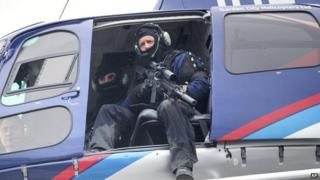 A police officer with a high powered weapon scans the ground from a helicopter for a gunman on 1 September 2014, after two people were killed and another injured in Ashburton, New Zealand