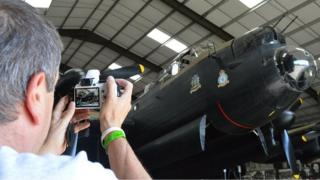 Man takes picture of Lancaster Bomber