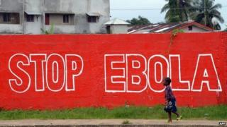 """A girl walks past a slogan painted on a wall reading """"Stop Ebola"""" in Monrovia - 31 August 2014"""