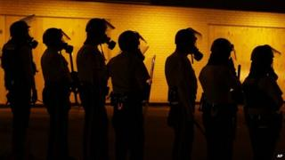 Police wearing gas masks stand by a wall in Ferguson, Missouri