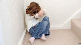 A young girl covers her face. File photo