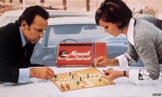Man and woman play board game Mensch Aergere Dich Nicht
