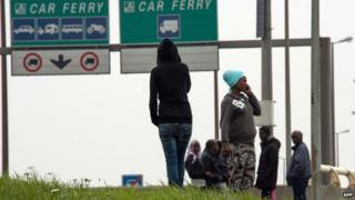 Migrants wait by side of road near Calais ferry port on 5 September 2014