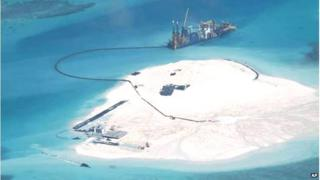 In this 25 Feb 2014 file photo taken by surveillance planes and released 15 May by the Philippine Department of Foreign Affairs, a Chinese vessel, top centre, is used to expand structures and land on the Johnson Reef, called Mabini by the Philippines and Chigua by China, at the Spratly Islands in the South China Sea, Philippines.