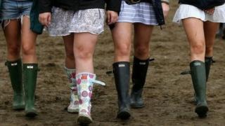 Girls walking in mud at festival