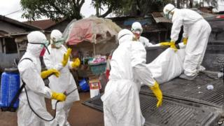 Health workers carry body of woman suspected to have died of Ebola in Clara Town, Monrovia (10 September 2014)