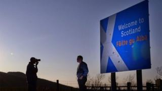 Peoiple take pictures beside a welcome to Scotland sign on the A68 near Carter Bar in Scotland