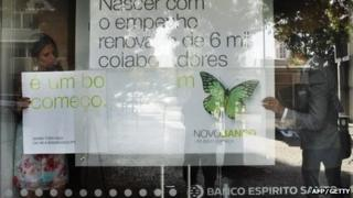 Staff changing the advertising sign to Nova Banco