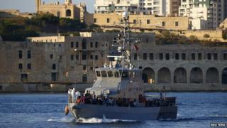"An Armed Forces of Malta (AFM) patrol boat carrying rescued migrants approaches the AFM""s Maritime Squadron base at Haywharf in Valletta""s Marsamxett Harbour, August 28"