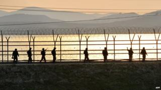 South Korean soldiers patrol along a military fence near the Demilitarized Zone