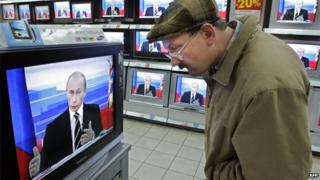 Russian TV viewer/President Putin on news - file pic