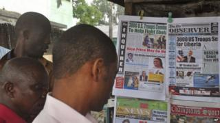 People read newspaper front pages in Monrovia