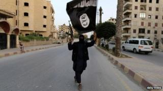 Islamic State fighter waves an IS flag in Raqqa, Syria - June 29, 2014