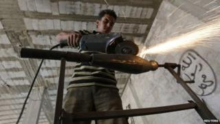 A rebel fighter makes improvised mortar shells inside a weapons factory in the southern countryside of Idlib 9 September 2014