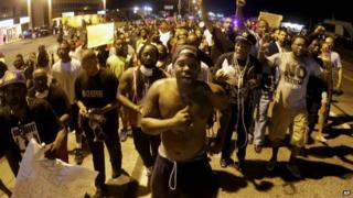 Ferguson protestors march through the streets at night
