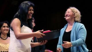 Dr Sonal Saraiya, left, accepts the Ig Nobel Prize for Medicine from Nobel Laureate Carol Greider during a performance at the Ig Nobel Prize ceremony at Harvard University, in Cambridge, Mass.,Thursday, Sept. 18, 2014.