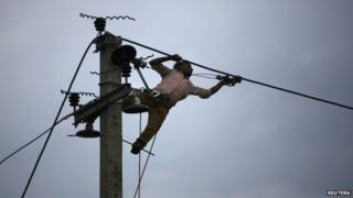 A worker installs new cables on an electric pole in Kathmandu