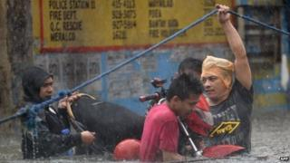 Manila residents hold onto a rope as they wade through floodwater (19 Sept 2014)