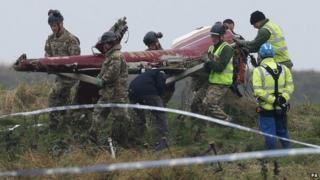 Crew carrying helicopter wreckage
