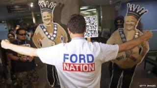 A supporter of Rob Ford stands in front of two cardboard cutouts of the Toronto Mayor