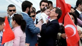 Turkish Prime Minister Ahmet Davutoglu celebrates with freed hostages in Ankara.