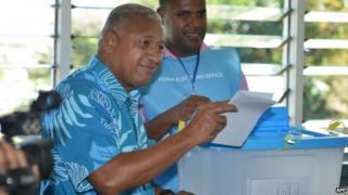 """This photo taken on 17 September 2014 shows Fiji's military strongman Voreqe """"Frank"""" Bainimarama (L) casting his election vote at the Vatuwaqa Public School in the capital Suva"""