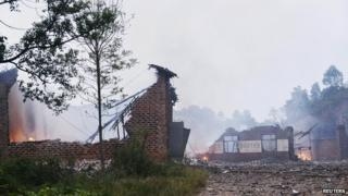 Ruins of a fireworks plant is seen on fire after an explosion in Liling, Hunan province on 22 September, 2014