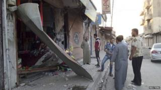 Men inspect damage to a shop after US air strikes in the Syrian city of Raqqa (23 September 2014)