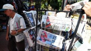 An Algerian man walks past newspapers in Tizi Ouzou, Algeria leading on the killing of Herve Gourdel