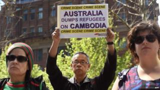 A protester holds up a placard at a rally in Sydney on 26 September 2014, opposing Australia's plan to start sending asylum-seekers to Cambodia by the end of the year.
