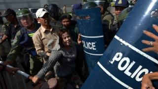 A Cambodian rights activist (C) clashes with police officials at a protest next to the Australian embassy in Phnom Penh