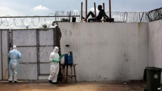 Health workers stand outside the Island Clinic Ebola isolation and treatment centre in Monrovia, Liberia, on 26 September