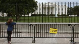 A young girl stands at a added security fence outside of the White House on 25 September 2014