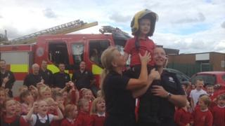 Liam Mansell is hoisted aloft by firefighters as fellow schoolchildren look on