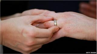 A close-up of hands as one person puts a wedding ring on the finger of another