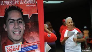 A woman stands next to a poster of Robert Serra on 22 September, 2010