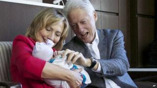 Bill and Hillary Clinton hold their granddaughter, Charlotte.