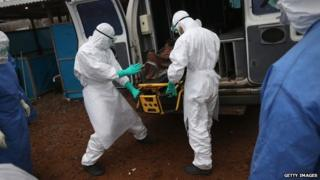 A burial team unloads an Ebola victim in Monrovia, Liberia, on 2 October 2014