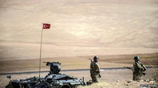 Turkish soldiers stand on a hill, facing the Islamic State (IS) fighters new position near the Syrian border at the south-eastern town of Suruc in the Sanliurfa province on 2 October 2014.
