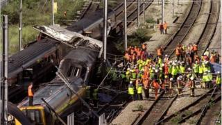 Rescue workers surrounding the wreckage of two trains which lie on rails in west London after a crash near Paddington Station