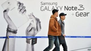 Pedestrians walk past a sign board advertising Samsung Electronics' Galaxy Note 3 smartphone at a railway station in Seoul