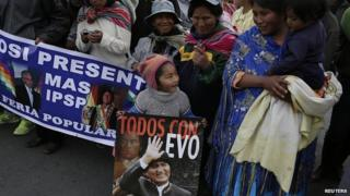 """A child holds a poster of Bolivia""""s President Evo Morales during a presidential election campaign meeting in La Paz"""