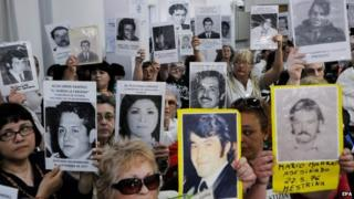 Relatives of victims of forced disappearance during the dictatorship period show photographs after learning of the sentence against former dictator Reynaldo Bignone in Buenos Aires on 7 October 2014